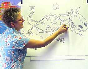 Lynne Chapman drawing a dragon at Lichfield Library