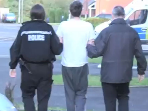 A man being led away during the raids