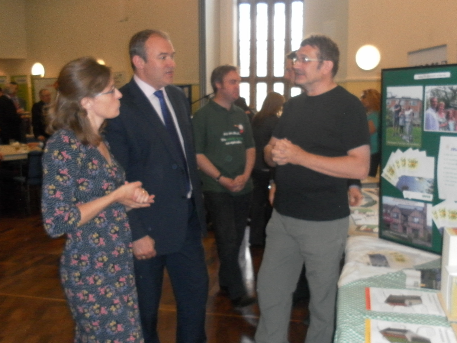 Kate Sadler (left) and Robin Tasker (right) talk with Ed Davey about the Goverment's Green Deal initiative