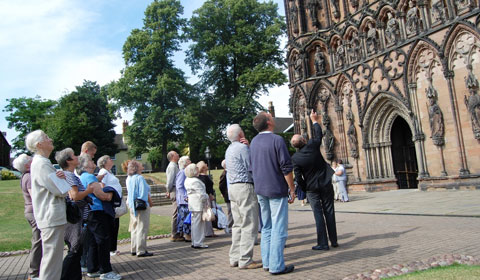 A guided tour group outside Lichfield Cathedral