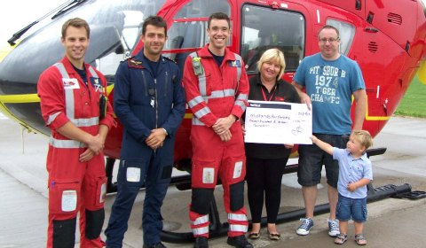 Tom Waters (Paramedic), James Benson (Pilot), Rob Till (Paramedic) and Jo Bailey  receive the cheque from Garry Mitchell and Callum