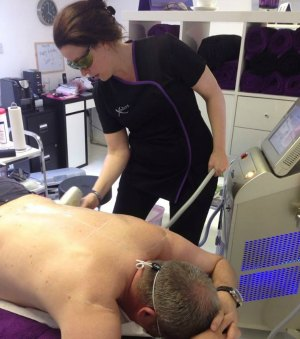 A male Xodos client having a back treatment