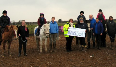 The cheque is handed over to riders and volunteers at Lichfield Riding for the Disabled