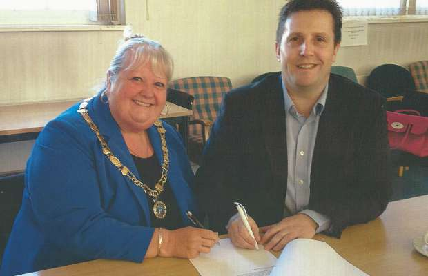 Burntwood Town Council chair Pam Stokes and leader Richard Mosson signing the lease on the Old Mining College Centre
