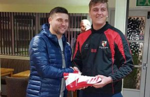 Ben Kibble-Spencer being presented with his new boots by Ben Foulds