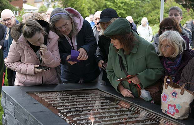 Visitors examining the new Peace Woodland plaque. Pic: Hannah Golding