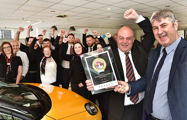 Staff at Bristol Street Motors Lichfield celebrate the award with Peter Hope (right) from Vauxhall Motors Ltd