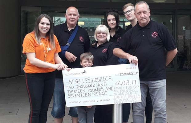 Beth Richardson from St Giles Hospice receiving the fundraising cheque from Mike Davies, Eunice Davies, Lauren Hardwick, Josh Allen, Tony Hardwick and Edward Hardwick