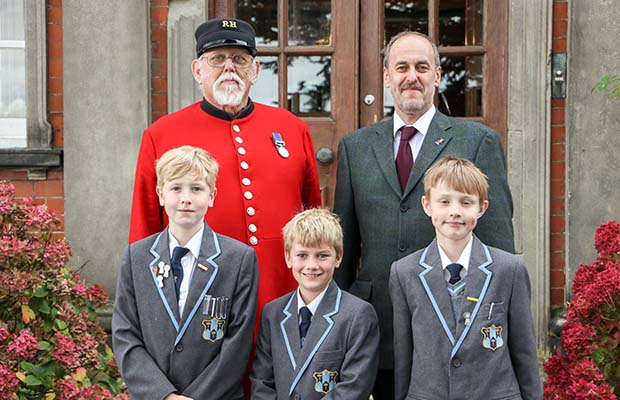 Chelsea Pensioner Peter Turner with Dr Daryl Brown and pupils William Haynes, Charlie Petty and Billy Bostock