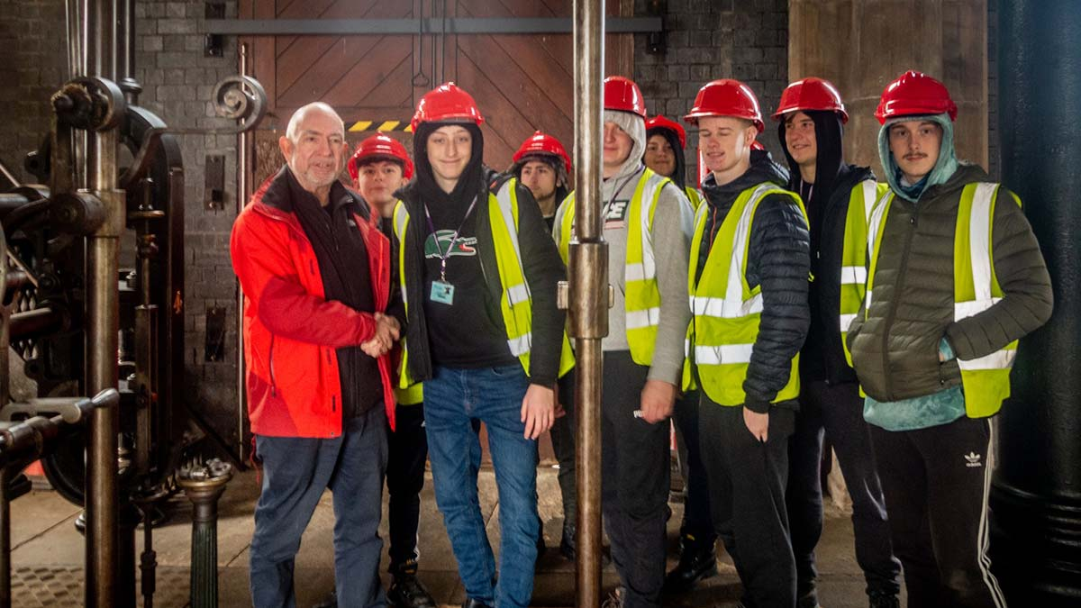 David Moore, chair of the Lichfield Waterworks Trust with apprentice electricians from Dudley Technical College
