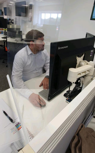 A member of staff using the Rollerscreen at their desk