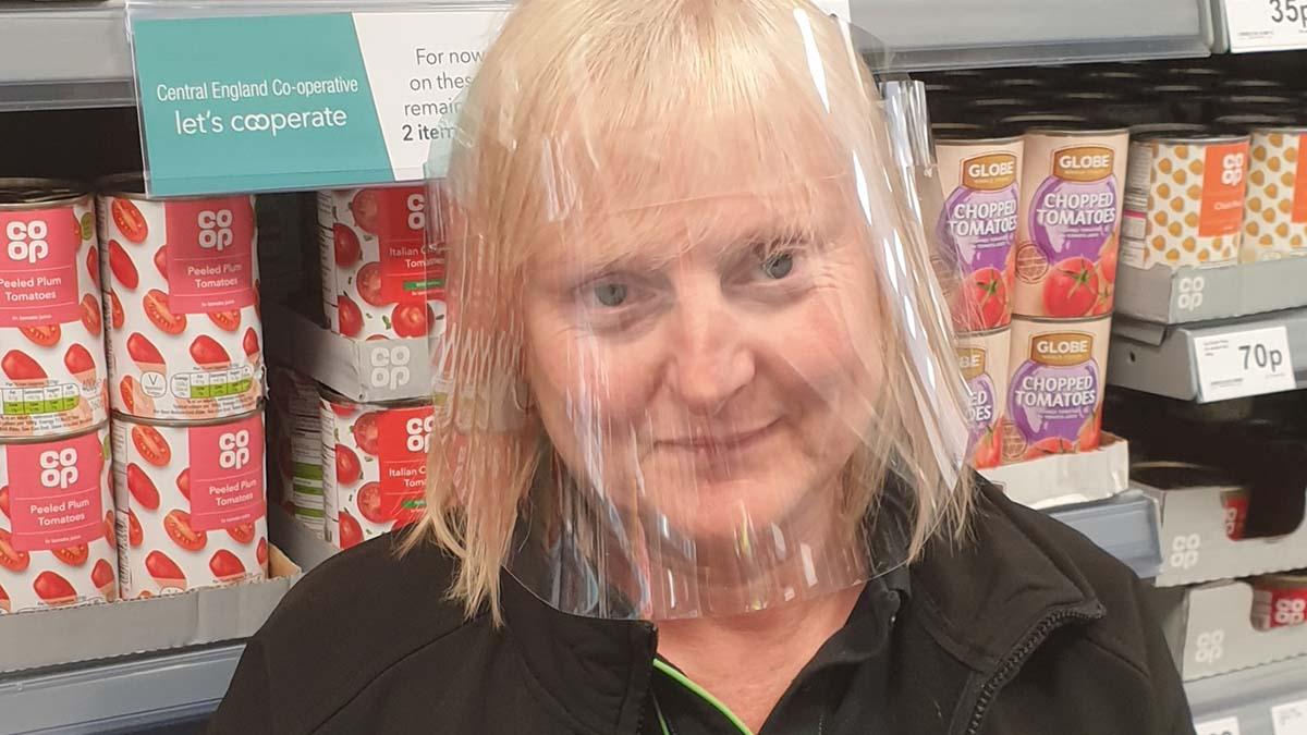 A Central England Co-op staff member wearing a visor