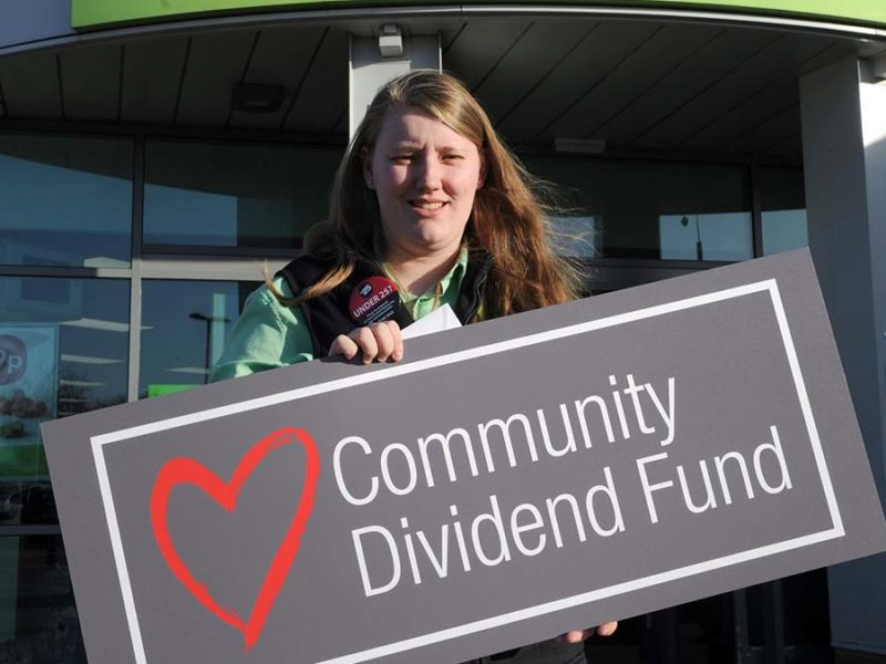 A Central England Co-op staff member holding a Community Dividend Fund sign