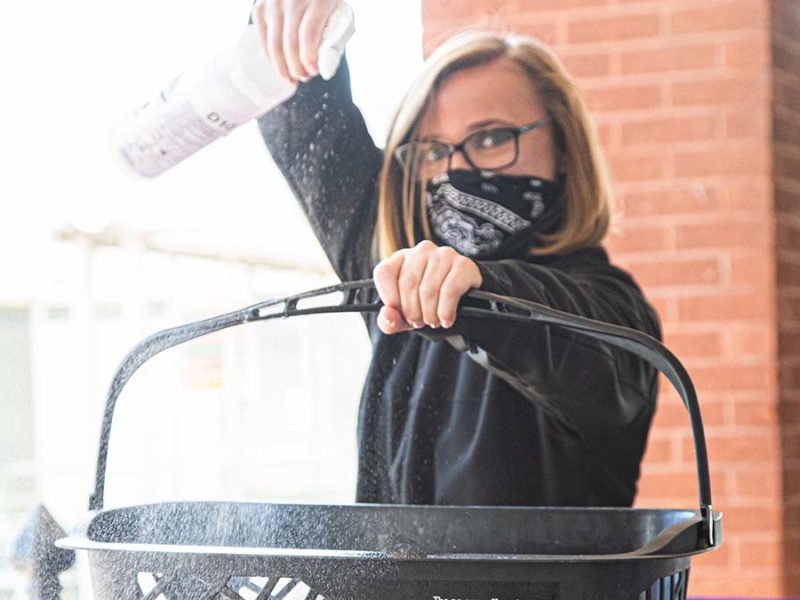 A Central England Co-op staff member wearing a mask while cleaning a basket