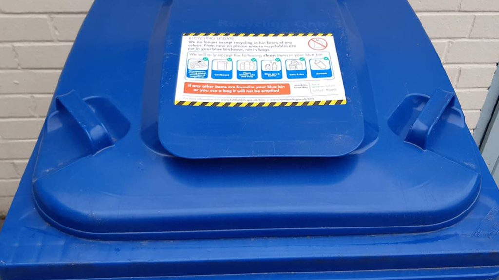 A new recycling guidance sticker on a blue bin