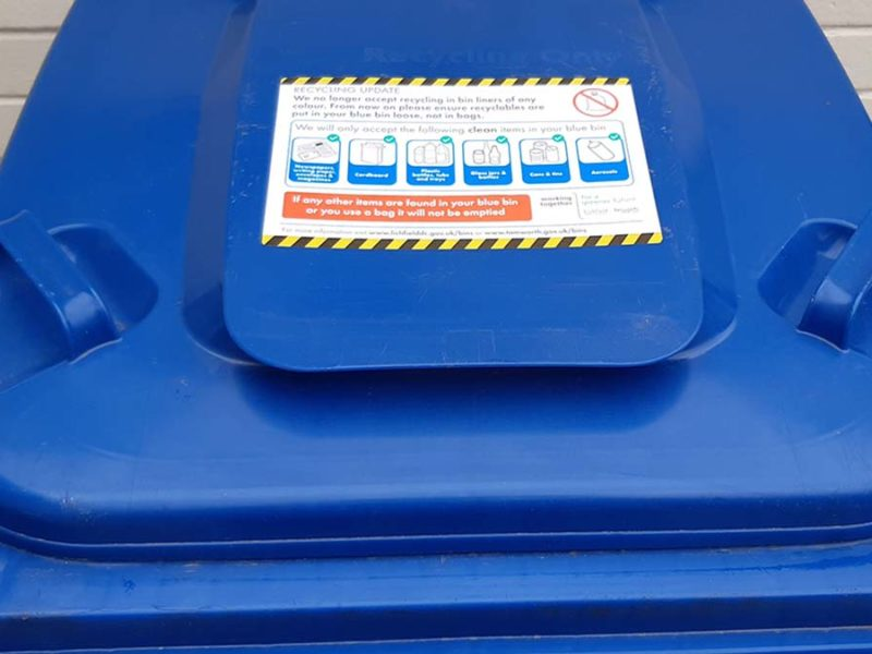 A new recycling guidance sticker on a blue bin