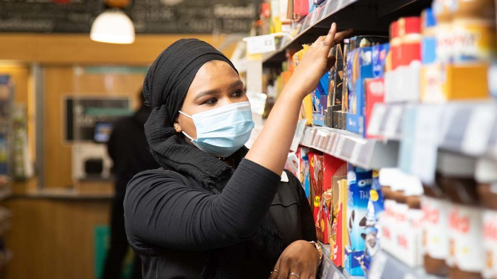 A Central England Co-op worker wearing a face mask