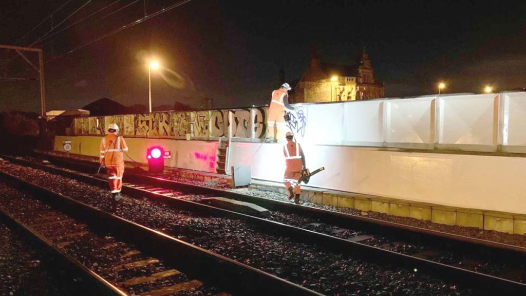 Crews cleaning graffiti from the side of the railway