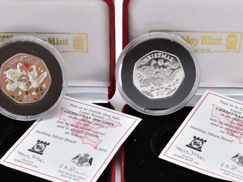 A boxed pair of Christmas 50p silver proofs which sold for £800