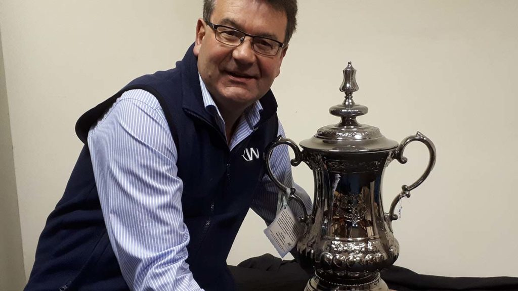 Auctioneer Richard Winterton with the replica FA Cup trophy