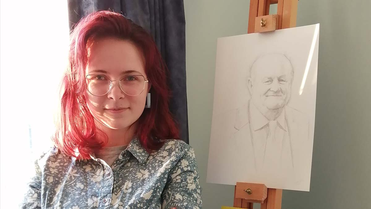 Sarah Devlin alongside her portrait of John Woodward OBE