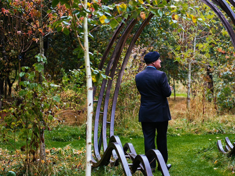 Terry Barnett beneath a curved oak sculpture leading to the centre of the Remembrance Glade