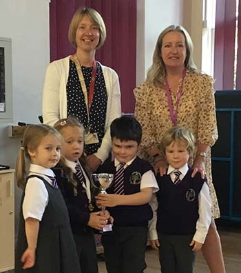 Liz Leyshon hands over the reading challenge trophy to pupils and headteacher Dee McLeary